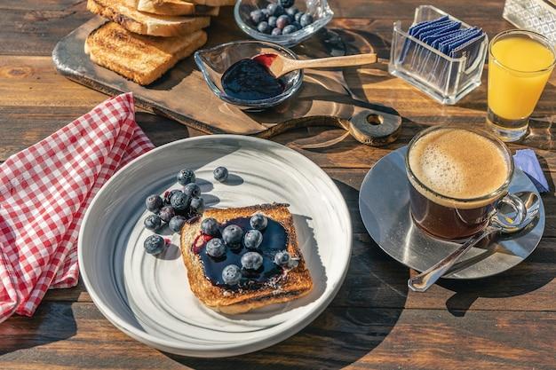 Tritata vista di una ricca colazione al sole con caffè, succo d'arancia, pane tostato, dolce ai mirtilli e mirtilli freschi. cibo sano e concetto di alimentazione naturale