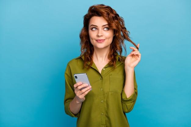Minded carino dolce adorabile bella donna tocco riccioli guarda copyspace usa il cellulare pensa pensieri decidere che tipo account social media indossare maglietta verde isolato sfondo colore blu
