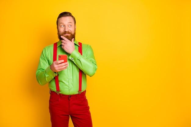 Minded uomo interessato usa smartphone tipo di testo chatt pensa pensieri decide scegli blogger post touch mento mano indossare bretelle rosse pantaloni pantaloni isolati brillante colore brillante