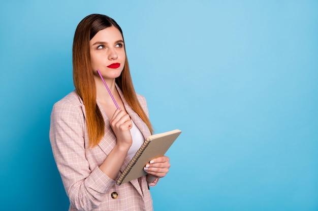 Mente intelligente ragazza tocca mento matita tenere quaderno guarda copyspace pensa
