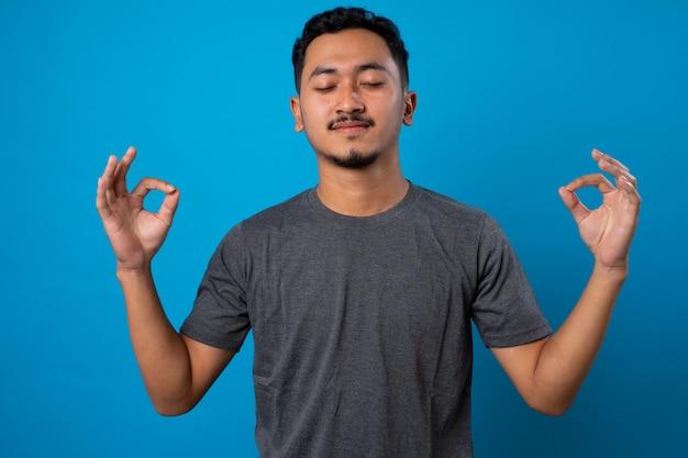 L'uomo pacifico consapevole medita indoor tiene le mani nel gesto mudra