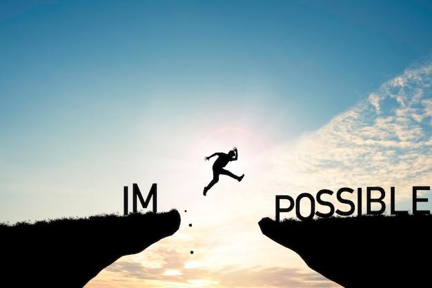 Concetto di mentalità, sagoma uomo che salta sopra formulazione impossibile e possibile sulla scogliera con cielo nuvoloso e luce solare.