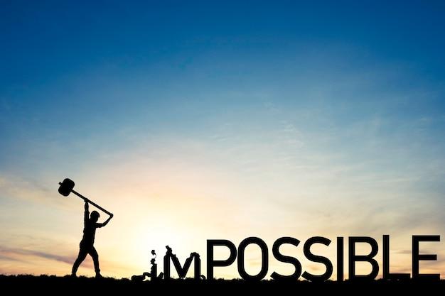 Concetto di mentalità, silhouette uomo fracassato con un martello per distruggere la formulazione impossibile e possibile sul cielo blu e sulla luce del sole.