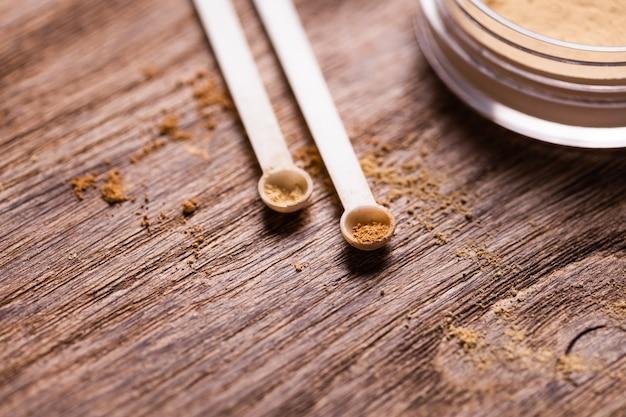 Polvere minerale di diversi colori con erogatore a cucchiaio per trucco su fondo in legno