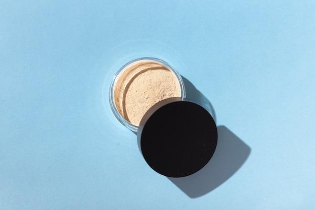 Fondotinta in polvere minerale isolato su sfondo blu prodotti di bellezza ecologici e biologici