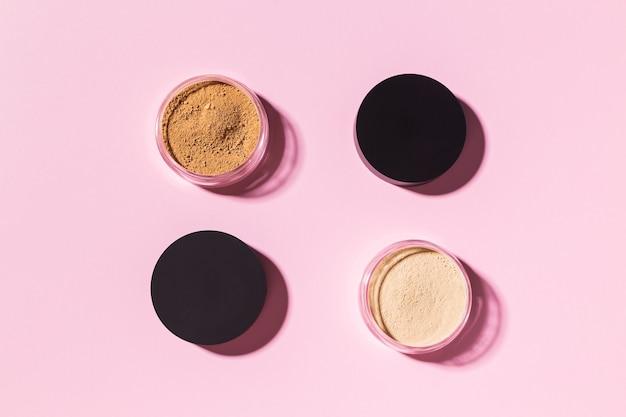 Fondotinta in polvere minerale isolato su uno sfondo rosa prodotti di bellezza ecologici e biologici