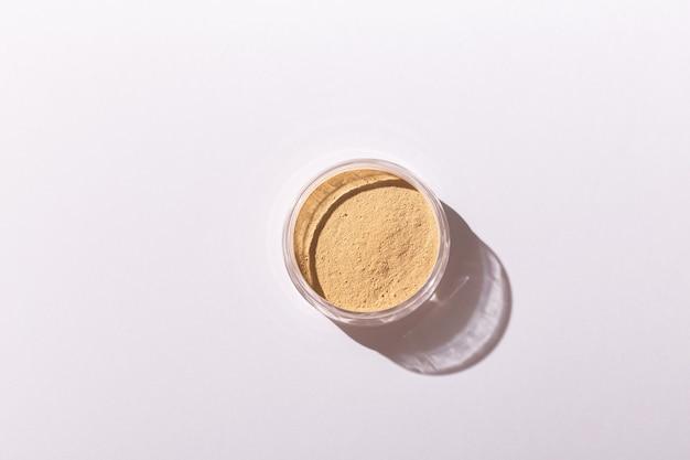 Fondotinta in polvere minerale isolato su uno sfondo bianco prodotti di bellezza ecologici e biologici