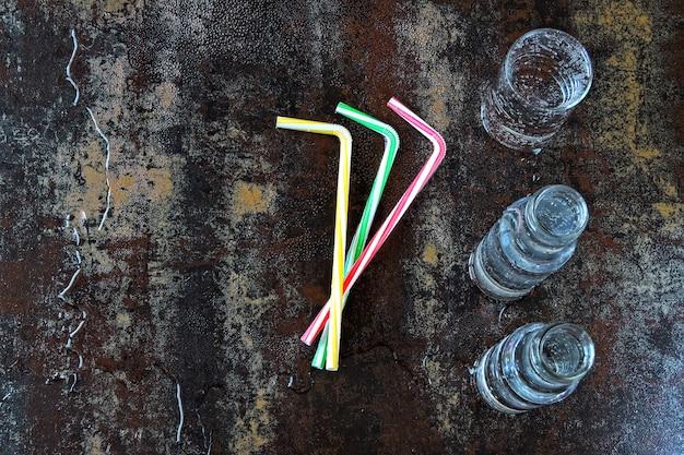 Acqua minerale in bottiglie di vetro e vetro. bere acqua in bottiglia con tubi da cocktail su un elegante sfondo squallido. il concetto di acqua minerale. acqua arricchita con vitamine e minerali.