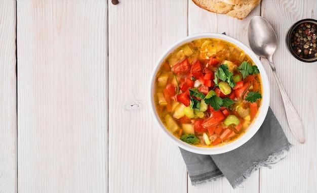 Zuppa di minestrone nel piatto bianco sulla tavola di legno bianca