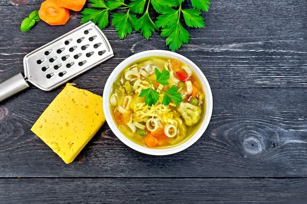 Minestrone con carne, sedano, pomodori, zucchine e cavolo cappuccio, piselli, carote e pasta in una ciotola bianca, formaggio, grattugia su fondo tavolato in legno nero sopra