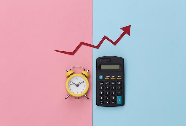 Mini sveglia e calcolatrice, freccia di crescita rossa su sfondo pastello rosa blu.