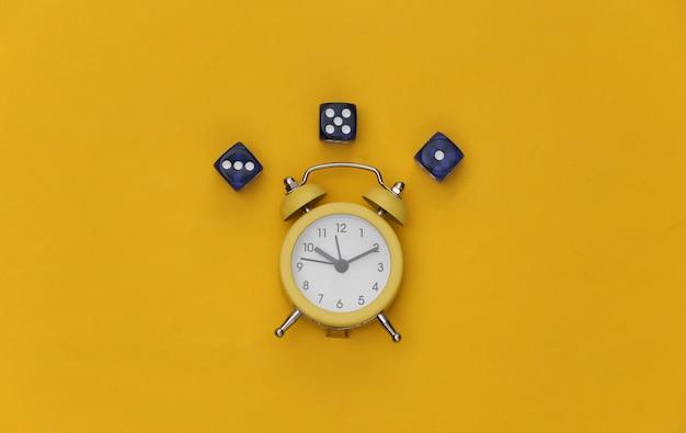Mini sveglia e dadi su sfondo giallo.