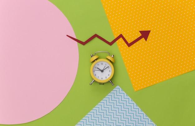 Mini sveglia e freccia di crescita rossa su sfondo di carta colorata creativa.