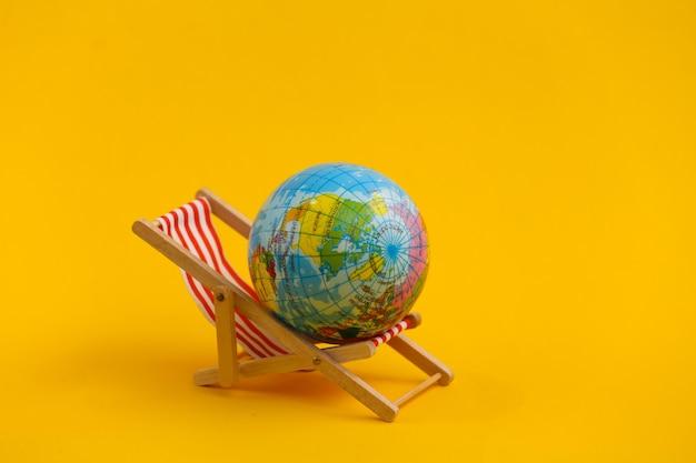 Mini sedia a sdraio da spiaggia e globo su giallo. simbolo di vacanze al mare e resort