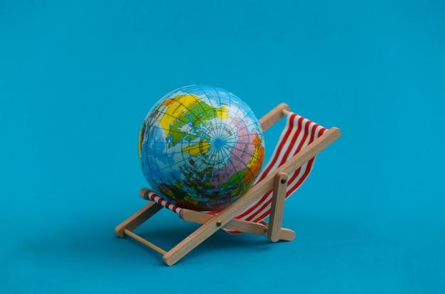 Mini sdraio da spiaggia con globo su sfondo blu. simbolo delle vacanze al mare, resort