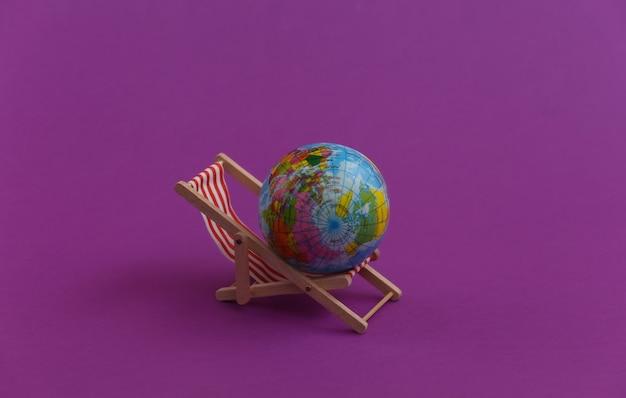 Mini sdraio da spiaggia con globo su viola. simbolo delle vacanze al mare, resort.