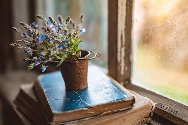 Mini mazzo di fiori di campo in un secchio decorativo su vecchi libri