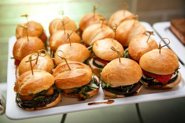 Selezione di tartine di mini hamburger su piatto di ardesia, catering per eventi