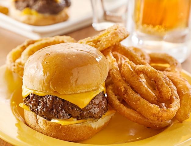 Mini hamburger con formaggio e anelli di cipolla serviti con birra.