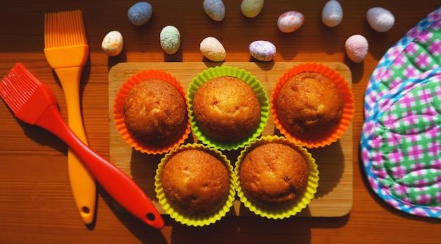 Mini torte decorate con uova, dolce di pasqua. mini muffin semplici in stampini di silicone colorati. cucina e concetto di cucina su fondo in legno