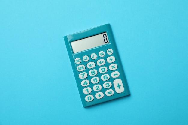 Mini calcolatrice su sfondo blu, primo piano
