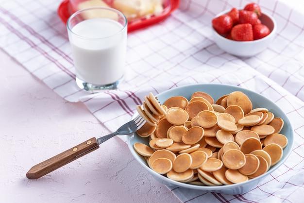 Mini frittelle di cereali in una ciotola blu con forchetta, fragole, bicchiere di latte su bianco