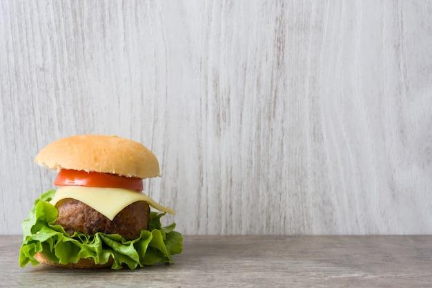 Hamburger del mini formaggio con le verdure sulla tavola di legno