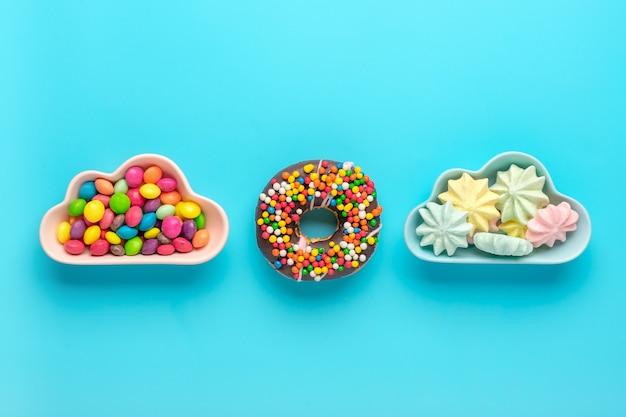Mini caramelle colorate in una ciotola a forma di nuvola con ciambelle isolate