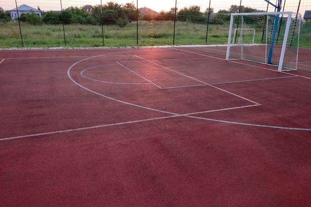 Mini campo da calcio con cancello a sfera e cestino circondato da alta recinzione protettiva.