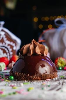 Mini torta di mousse al cioccolato francese sul tavolo di caramelle. dessert glassato a specchio