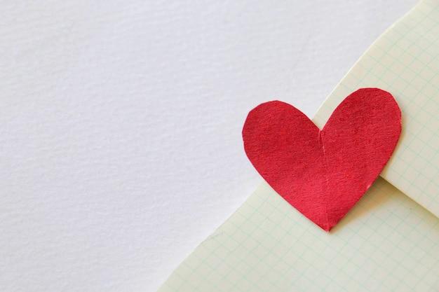 Mini cuore sulla trama dello sfondo della carta. fogli bianchi di carta a righe da un blocco su sfondo grigio