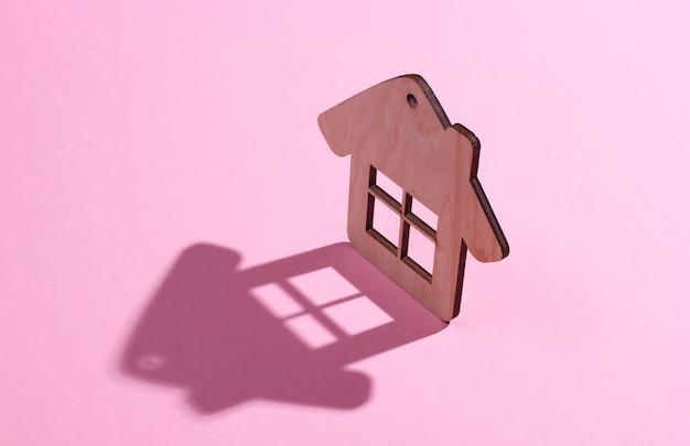 Figura di mini casa su sfondo rosa pastello. studio girato con ombra