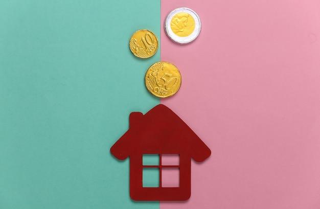 Mini figurina casa con monete su un pastello blu-rosa. bilancio familiare