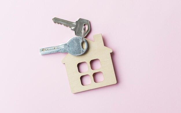 Statuetta mini casa con chiavi su una scrivania rosa
