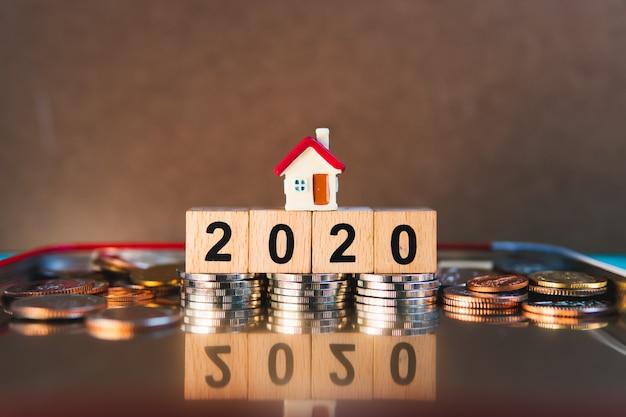 Mini casa sull'anno 2020 del blocco di legno con le monete della pila facendo uso di come concetto finanziario del bene immobile della proprietà e finanziario