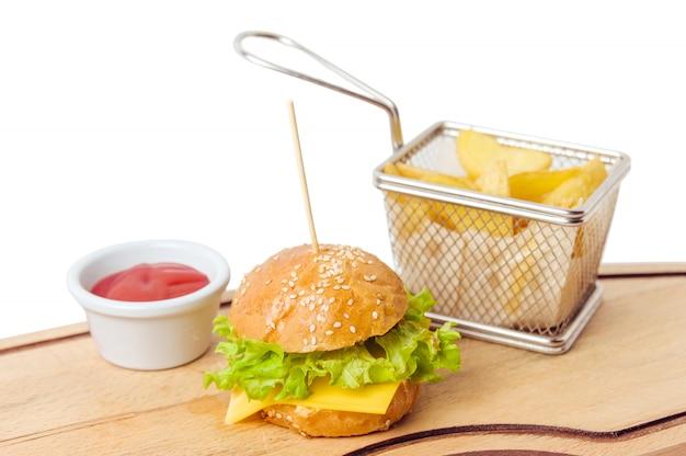 Mini hamburger del bambino con succo e la patata isolati
