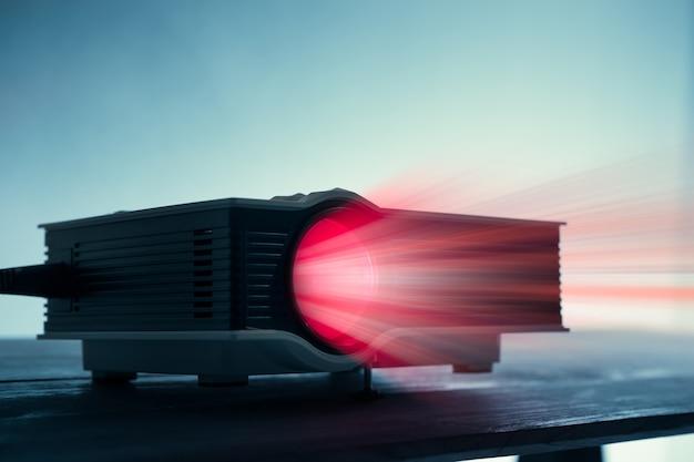 Mini proiettore a led sul tavolo in sfondo scuro home theater proiettore tono blude.