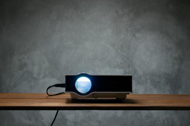 Mini proiettore principale sulla tavola di legno in un concetto del teatro domestico del proiettore della stanza.