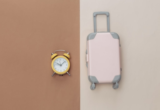 Mini bagaglio e sveglia su fondo beige marrone.
