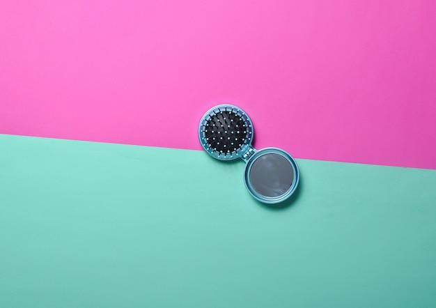 Mini pettine a specchio su uno sfondo di menta rosa al neon. vista dall'alto.