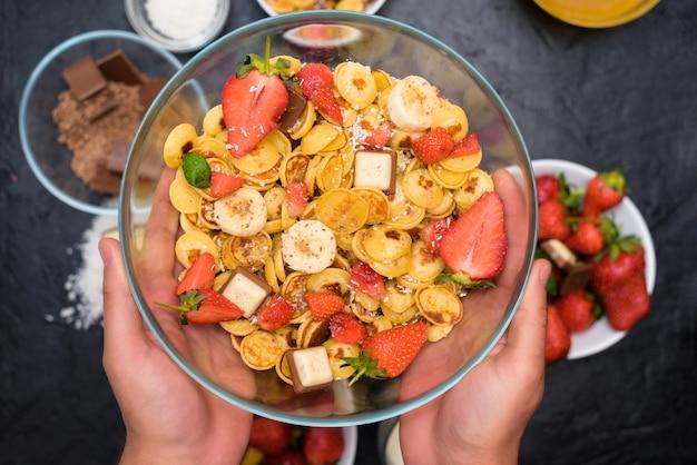 Ciotolina per mini pancake con fragole fresche, cioccolato alla banana, scaglie di cocco e miele in piccoli piatti.