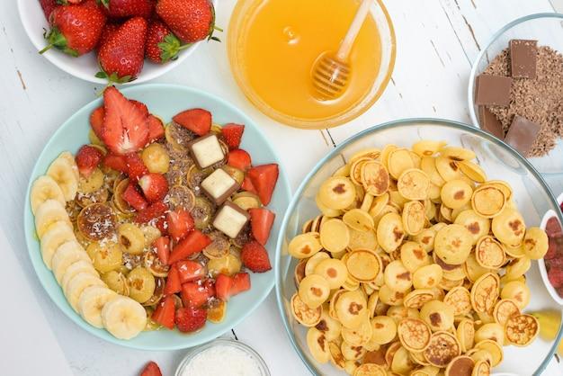 Ciotola di cereali mini pancake con fragole fresche, banana e cioccolato, scaglie di cocco e miele