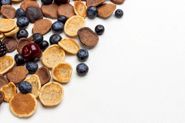 Mini frittelle e frutti di bosco su sfondo bianco. lay piatto. copia spazio