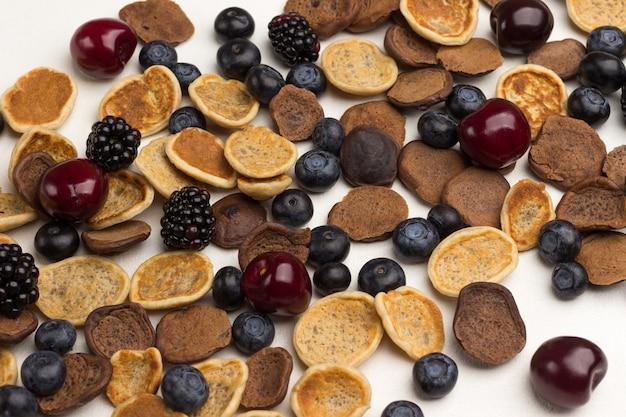 Mini frittelle e frutti di bosco su superficie bianca. lay piatto. avvicinamento