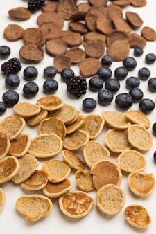 Mini frittelle e frutti di bosco su superficie bianca. lay piatto.