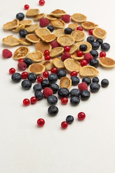 Mini frittelle e frutti di bosco su superficie bianca.