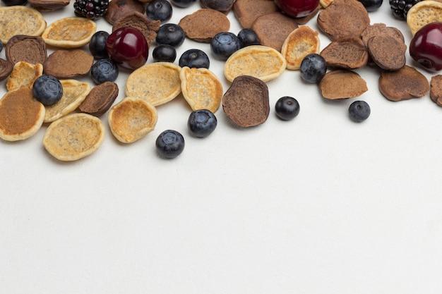 Mini frittelle e frutti di bosco su bianco
