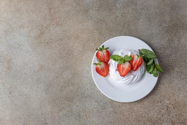 Mini pavlova torte di meringa con fragole e menta su un piatto