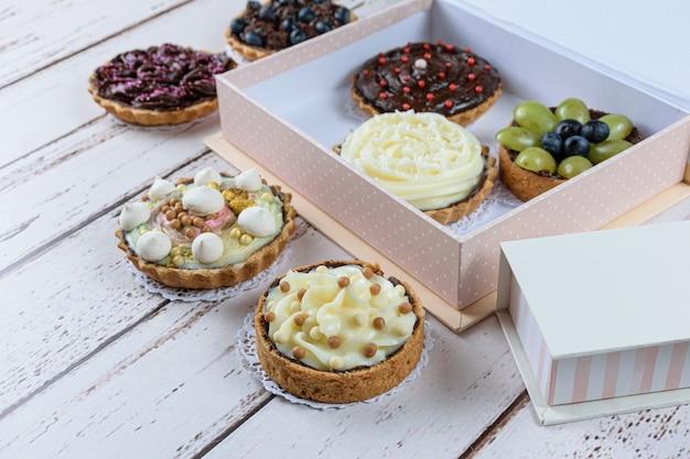 Mini crostata con impasto burroso, ripieno di ganache al cioccolato e crema al cocco. circondato da altre torte e scatole.
