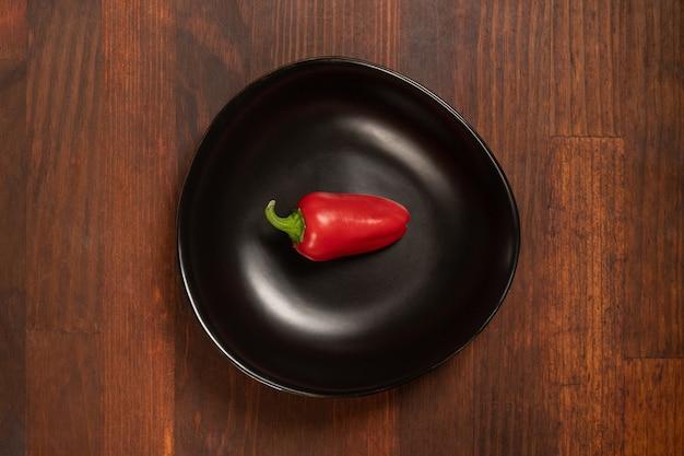 Mini peperone rosso che risiede in un bawl nero isolato su fondo di legno. vista dall'alto
